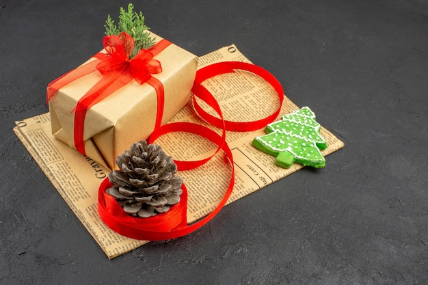 Bottom view xmas gift in brown paper branch fir ribbon on newspaper xmas ornaments on dark background xmas photo