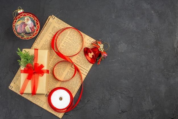 Vista dal basso regalo di natale in nastro di abete ramo di carta marrone su ornamenti di natale di giornale su oscurità