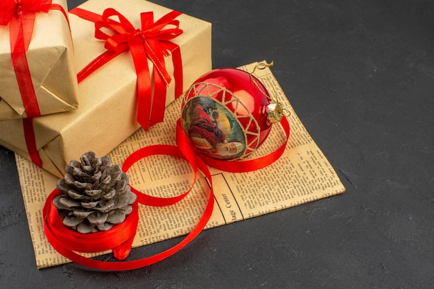 Bottom view xmas gift in brown paper ribbon xmas tree toy on newspaper on dark background