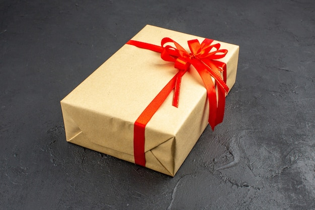 Bottom view xmas gift in brown paper tied with red ribbon on dark background free space