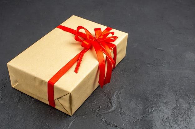 暗い自由空間に赤いリボンで結ばれた茶色の紙の底面のクリスマスプレゼント
