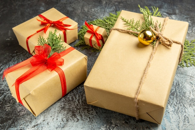 Vista dal basso regalo di natale piccoli regali rami di pino su grigio