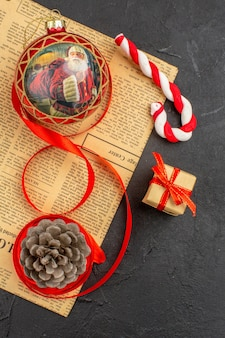 Bottom view xmas gifts in brown paper ribbon xmas tree toy on newspaper on dark background