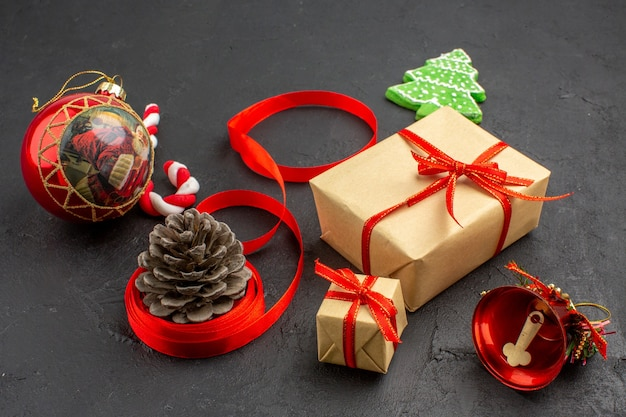 Bottom view xmas gifts in brown paper ribbon xmas tree toy on newspaper on dark