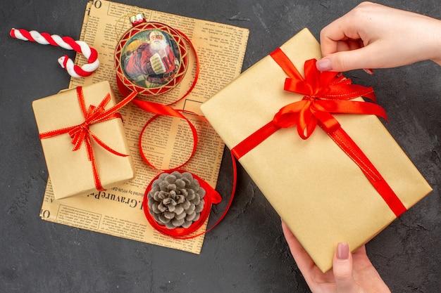 어두운 배경에 신문에 갈색 종이 리본 크리스마스 트리 장난감의 아래쪽 보기 크리스마스 선물