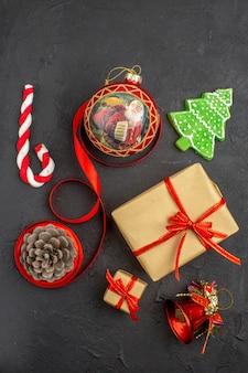 暗い上の新聞の茶色の紙のリボンのクリスマスツリーのおもちゃの底面図のクリスマスプレゼント