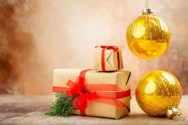 Рождественские подарки в коричневой бумажной ленте, рождественские елочные игрушки на газете на бежевом фоне, вид снизу