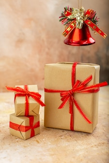 베이지색 신문에 갈색 종이 리본 크리스마스 트리 장난감의 아래쪽 보기 크리스마스 선물