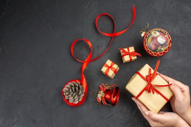 ベージュの新聞の茶色の紙のリボンのクリスマスツリーのおもちゃの底面図のクリスマスプレゼント