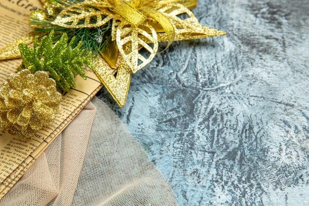 Vista dal basso ornamenti appesi di natale su scialle beige di giornale su sfondo scuro posto libero