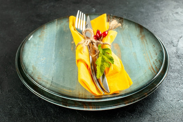 Bottom view yellow napkin knife and fork tied with rope on plates on black table