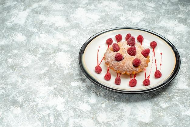 Вид снизу ягодный торт на белой овальной тарелке на серой поверхности копией пространства