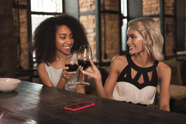 ボトムアップ。バーのカウンターに座って乾杯しながらグラスワインをチリンと鳴らすゴージャスな女性の友人