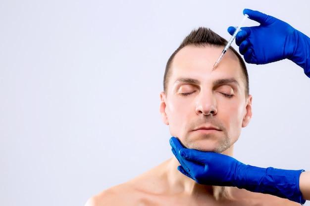 Ботулиническая терапия. крупным планом руки человека, вводя шприц с ботоксом для лечения лица. эстетокс. диспорт