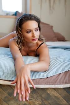 Boudoirの写真。ベッドの上でポーズをとって下着姿の美しいほっそりした若い女性