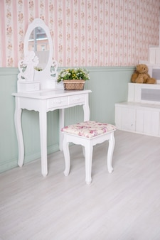 Boudoir table. details of the interior of the bedroom for girls and make-up, hairstyles with a mirror.