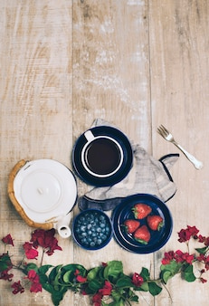 Bougainvillea pink flower; strawberries; blueberries; teapot and coffee cup on wooden table