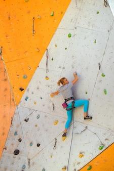 Bouldering, girl climbing up the wall