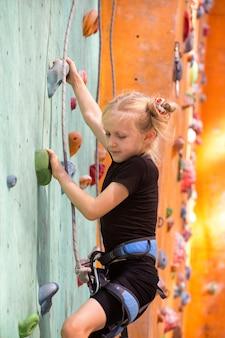 Bouldering, little girl climbing up the wall