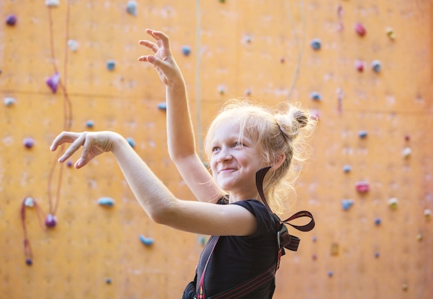 Bouldering, little girl fooling around on the background of climbing wall