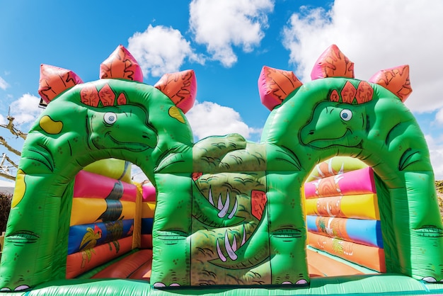 Bouncy castle in the shape of dinosaurs in a children's playground outdoors.