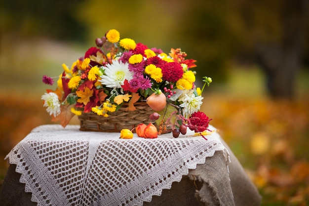 Bouquet of autumn flowers in the basket on the table in rustic style. autumn time.