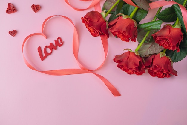 Bouquet of beatiful red roses and love lettering