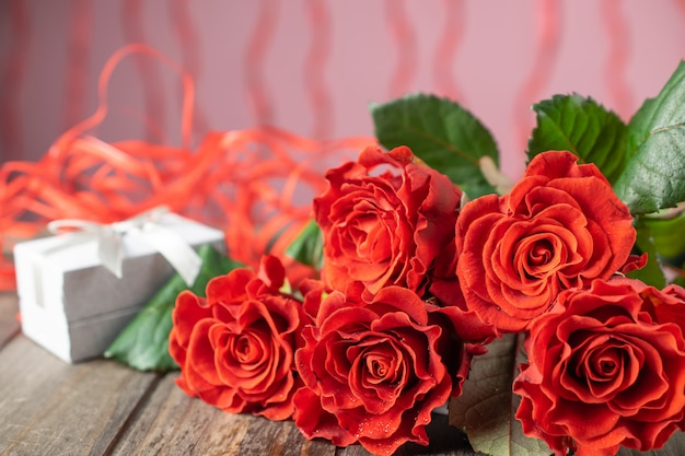 Bouquet of beatiful red roses and a present box