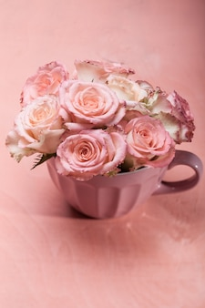Bouquet of beautiful fresh pink roses in a cup