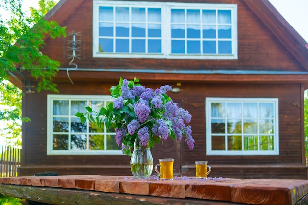 A bouquet of beautiful lilacs in a glass vase stands on a wooden table. wooden cottage in the forest.