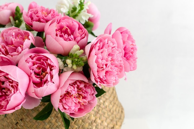 Bouquet of beautiful pink peonies in straw basket