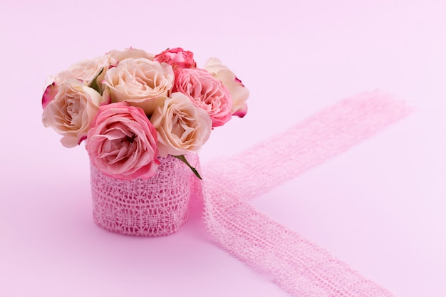 A bouquet of beautiful roses stands in a small bucket on a lace ribbon on a pink background