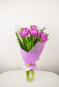 Bouquet of beautiful violet lush tulips in a vase