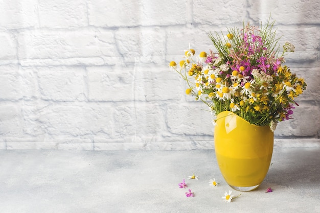 Bouquet of beautiful wildflowers in vase on a gray surface with copy space.