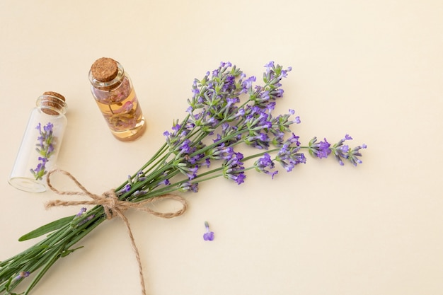 Bouquet of blooming lavender and small glass bottles with essential lavender oil and flowers