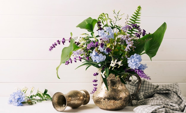Bouquet of blooms in vase near pitcher on table