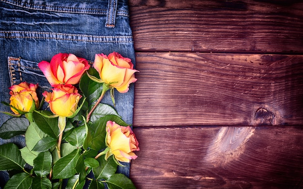 Bouquet of blossoming roses on blue pants jeans