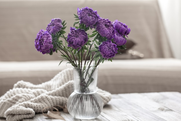 Un mazzo di crisantemi blu in un vaso di vetro sul tavolo all'interno della stanza.