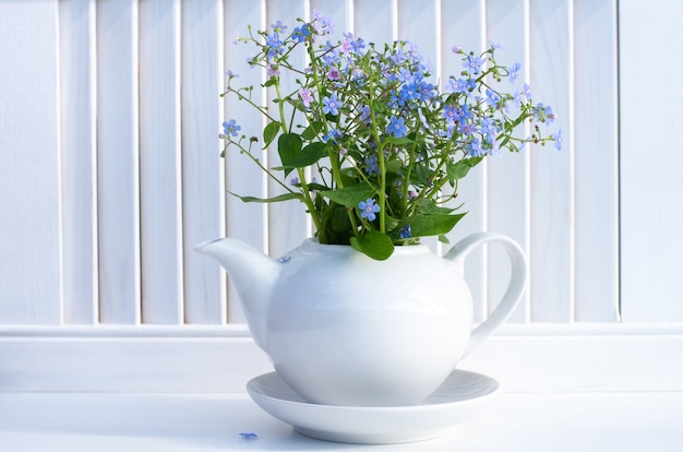 A bouquet of blue forget-me-nots in a white ceramic teapot