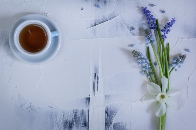 Bouquet of blue muscaries flowers and cup of tea on white background.