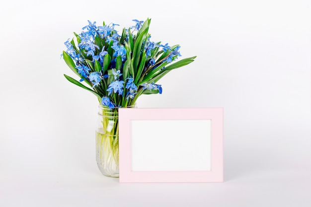 Bouquet of blue spring flowers and a pink frame mock up