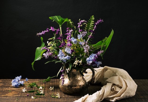 Bouquet of blue and violet blooms in vase on table