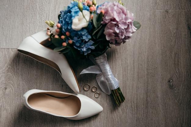 꽃다발, 신부 신발 및 결혼 반지가 바닥에 놓여 있습니다.