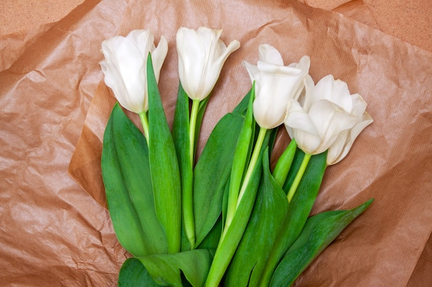 Bouquet of bright delicate white tulips with bright green foliage in craft paper on a background of wood plate