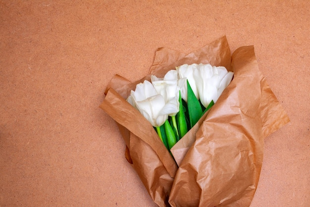Bouquet of bright delicate white tulips with bright green foliage in craft paper on wood plate