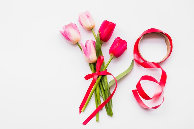 Bouquet of bright fresh flowers on stems near roll of ribbon