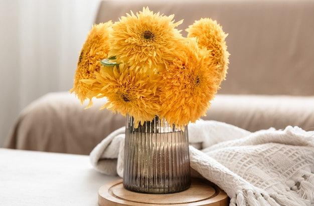 A bouquet of bright sunflowers in a glass vase on a blurred background in the interior of the room.