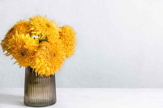 A bouquet of bright sunflowers in a glass vase on a blurred white background, copy space.