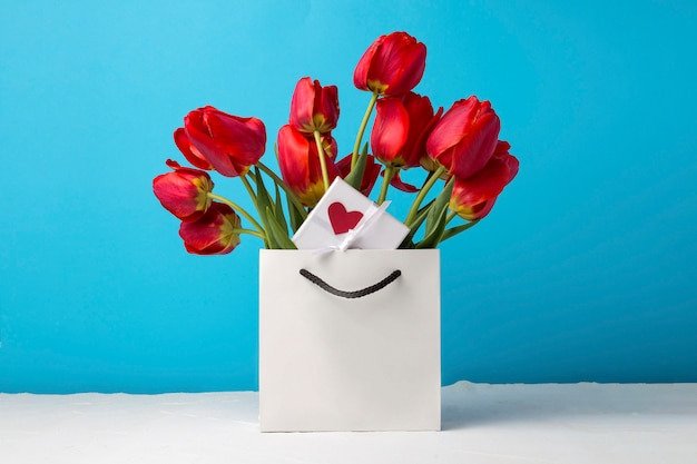 Bouquet of brightly red tulips, a small white gift box with a red heart in a white gift bag on a blue. conception of congratulations and a gift