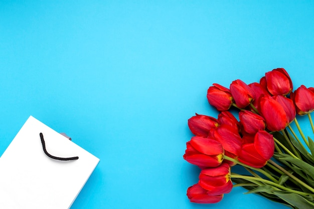 Bouquet of brightly red tulips in a white gift bag on a blue background. conception of congratulations and a gift. flat lay, top view